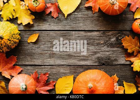 Les feuilles tombées et les citrouilles sur fond de bois avec copie espace pour texte. vue d'en haut. l'arrière Banque D'Images