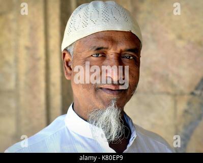 Homme musulman indien d'âge moyen avec bouc musulman portant une casquette de prière islamique blanche (taqiyah) Banque D'Images