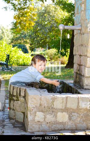 Happy boy lave-mains dans un parc Banque D'Images