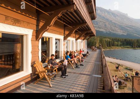 Les clients du lodge swiftcurrent assis sur le balcon donnant sur le lac et admirer le coucher du soleil sur la Banque D'Images