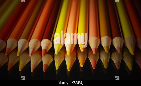 Crayons de couleur jaune et orange avec réflexion sur fond noir Banque D'Images