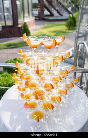 Pyramide de verres lors de célébration. cocktails colorés près. une partie sur le coucher du soleil