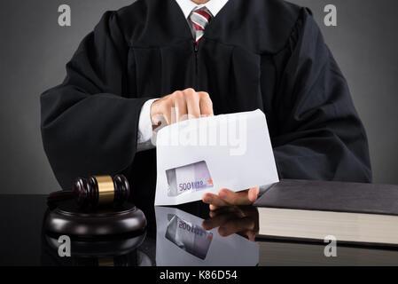 Close-up du juge de mettre l'argent dans une enveloppe au bureau, dans la salle d'audience Banque D'Images