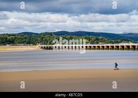 Deux personnes marchant sur le sable au-dessous Arnside Viaduc quand la marée se retire, Arnside, Cumbria, Royaume Banque D'Images