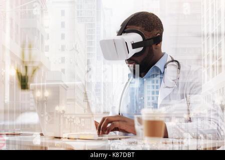 Médecin occupé avec masque virtuel à l'aide d'un ordinateur portable Banque D'Images