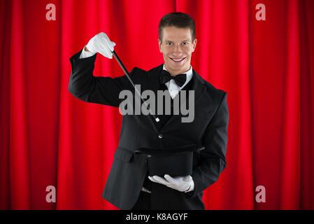 Les jeunes professionnels magicien montrant tour de magie avec chapeau