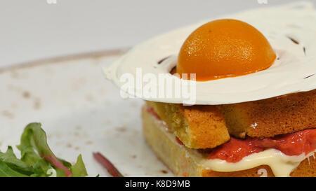 Gâteau éponge victoria avec straberries, confiture et crème fouettée avec une pièce sur un fond blanc Banque D'Images