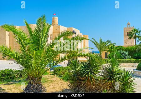 La vue sur les murs en pierre de la vieille forteresse ribat et minaret de la grande mosquée dans le jardin luxuriant Banque D'Images