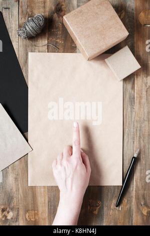 La femelle montre quelque chose sur la feuille de papier craft Banque D'Images