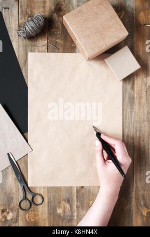 La main féminine écrire quelque chose sur la feuille de papier craft Banque D'Images