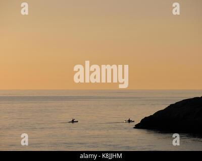 Deux personnes faisant du kayak au coucher du soleil à l'extérieur de Klåva, Hönö, l'archipel de Göteborg, en Suède.