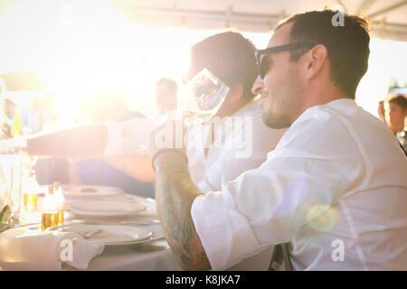 Tourné en plein air de beau jeune homme boire du vin lors d'une fête d'été avec un ami