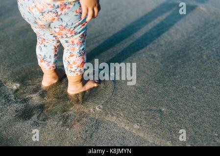 Bébé jouant avec des vagues sur la plage.croissance et d'apprentissage.concept concept familiales et parentales Banque D'Images