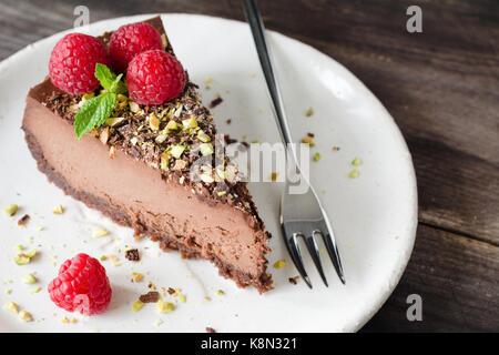 Tranche de gâteau au chocolat décoré de pistaches, framboises et feuille de menthe sur plaque blanche sur fond de Banque D'Images