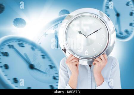 Man in suit holding a réveil contre digital image composite d'horloges de mur Banque D'Images