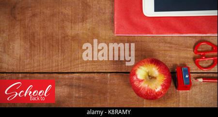 Retour à l'école texte sur fond blanc contre vue aérienne de apple avec mètre et tablette Banque D'Images
