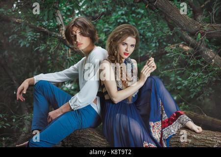 Jeune couple d'elfes dans l'amour de l'emplacement sur la branche dans une forêt magique sur la nature. conte de Banque D'Images
