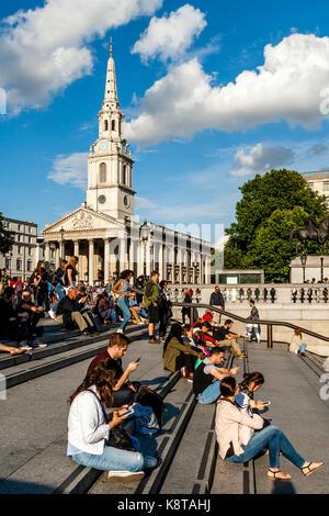 Les jeunes gens assis sur les marches de Trafalgar square avec l'église de st martin-in-the-champs dans le contexte, Banque D'Images