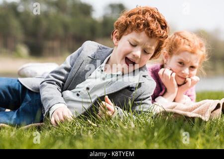 Frères et sœurs lying on grass Banque D'Images