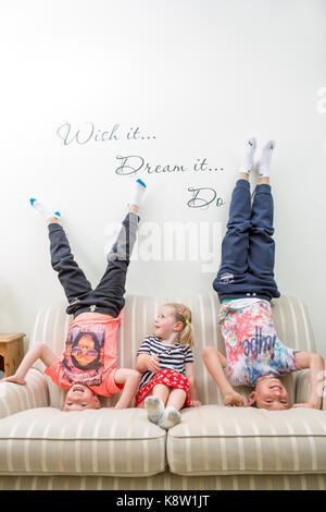 Les enfants faisant la tête sur le canapé Banque D'Images