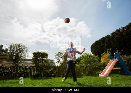 Garçon jouant au football à la maison Banque D'Images