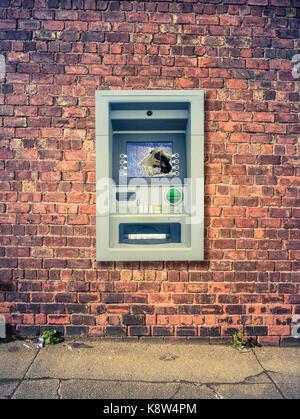 Un distributeur automatique de vandalisme contre un mur de brique rouge grunge Banque D'Images