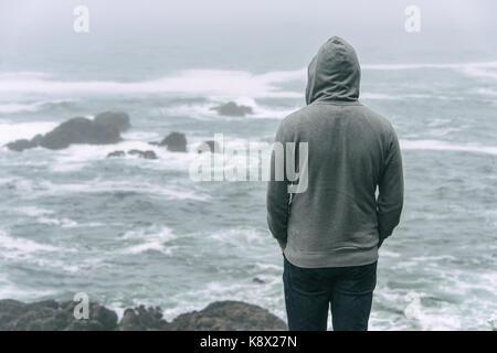Triste et solitaire homme debout en face de l'océan pacifique et à la recherche à la mer agitée sur l'île de Vancouver. Banque D'Images