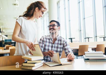 Les jeunes étudiants attrayant de son temps en bibliothèque Banque D'Images