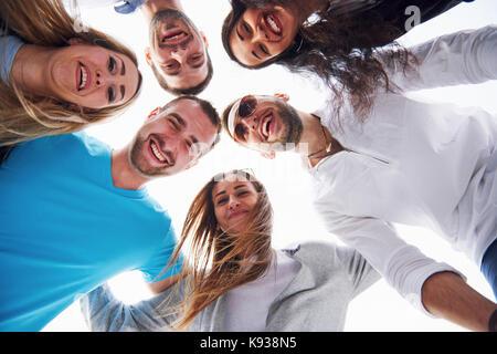 Portrait d'un groupe de jeunes gens assis sur le bord de la jetée, à l'extérieur dans la nature. les amis en faisant Banque D'Images