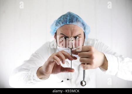 Barbu fou doctor in a white coat et vieille seringue Banque D'Images