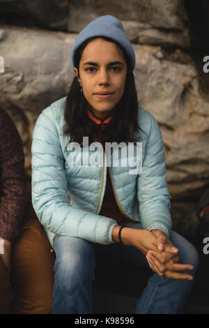 Portrait of smiling woman sitting on rock