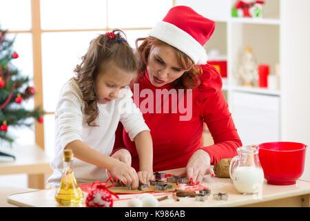 Heureuse femme et enfant fille coupant les cookies de noël hors de pâte ensemble Banque D'Images