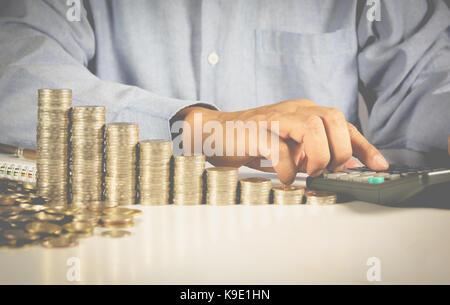 Main de l'homme d'affaires font pression sur la calculatrice avec pièces en pile sur la table. l'homme en appuyant Banque D'Images