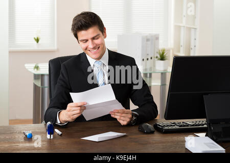 Young businessman smiling alors que reading paper at desk in office Banque D'Images