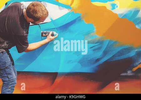 Photo dans le processus d'élaboration d'un modèle de graffiti sur un vieux mur de béton. jeune blonde aux cheveux long guy trace un dessin abstrait de couleurs différentes.