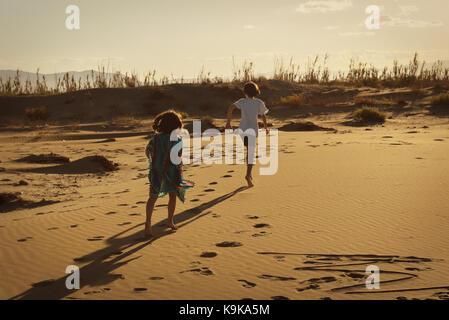 Garçon et fille courir à l'état sauvage sur une plage de sable fin au coucher du soleil laissant footprints Banque D'Images