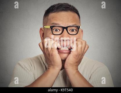 Closeup portrait portrait young nerdy guy avec des lunettes de mordre ses ongles vous regarde avec envie irrésistible Banque D'Images