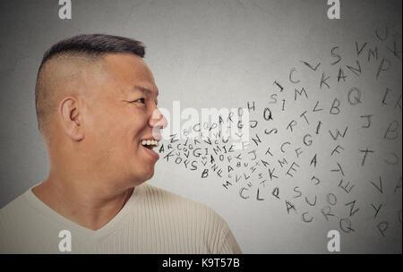 Vue de côté portrait young handsome man avec lettres de l'alphabet qui sortent de la bouche ouverte de fond de mur Banque D'Images