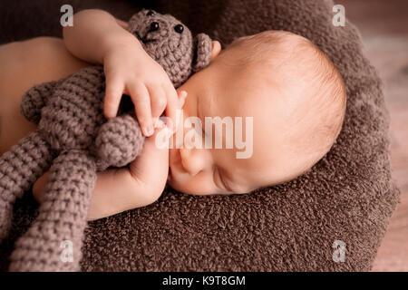 Bébé nouveau-né de dormir dans une belle pose avec un petit ours Banque D'Images