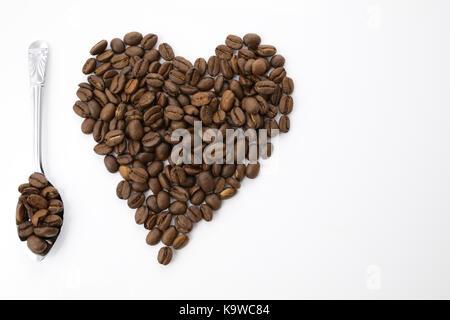 Grains de café en forme de coeur avec une cuillère argentée isolée sur fond blanc. J'adore le concept du café Banque D'Images