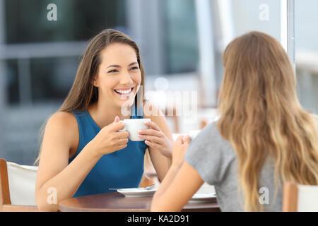 Deux amis heureux d'avoir une conversation informelle dans un bar terrasse Banque D'Images