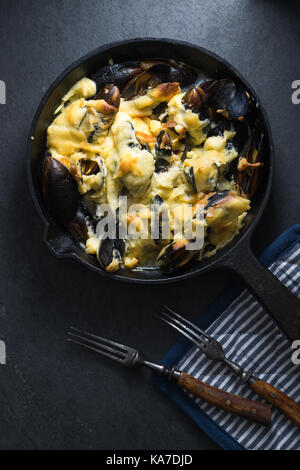 Les moules avec une sauce au fromage dans un poêlon, serviette et verticale des fourches Banque D'Images