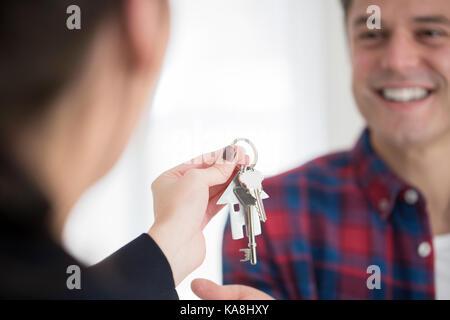 Récupérez les clés à l'homme nouvelle maison de female realtor Banque D'Images