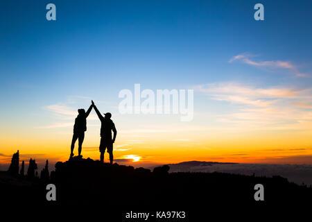 Les randonneurs en couple succès coucher de montagnes, accompli avec les bras tendus. Homme et femme sur rocky mountain Banque D'Images