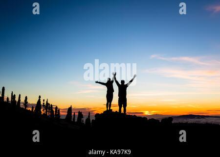 Couple d'équipe de l'escalade et de la montagne la plus élevée d'atteindre. L'équipe d'alpinistes Silhouette sur Banque D'Images