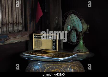 La vie toujours avec des appareils ménagers. Still Life with vieille radio et ventilateur électrique, magazine et Banque D'Images