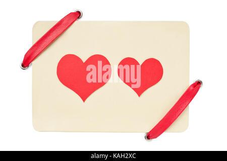 Carte de la Saint-Valentin avec ruban rouge isolé sur fond blanc. deux coeurs rouges - symbole de l'amour Banque D'Images