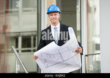Jeune ingénieur with hard hat holding plan directeur dans ses mains