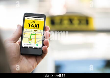 Close-up of personne réservation taxi sur smart phone