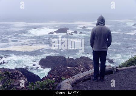 Homme seul, debout devant l'océan pacifique et à la recherche à la mer agitée sur l'île de Vancouver. Banque D'Images
